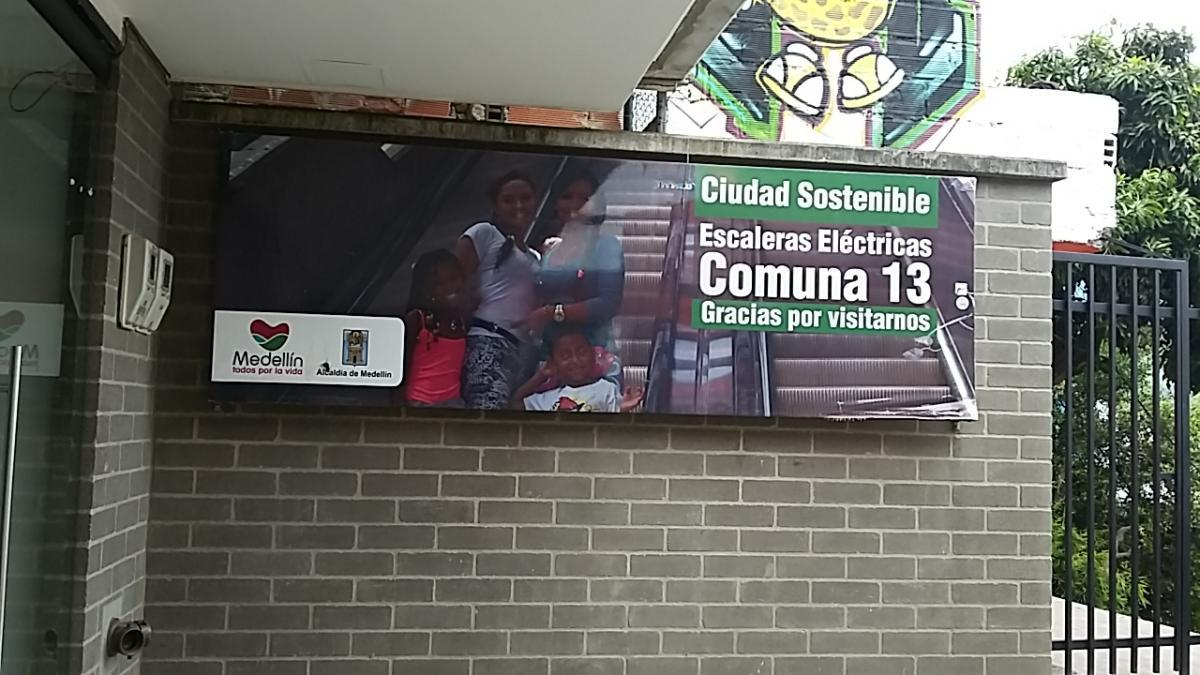 Welcome to Comuna 13 sign by escalator; woman in white t-shirt was our guide