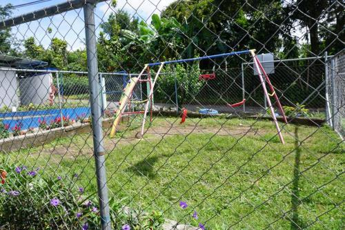 Very small fenced area with swings