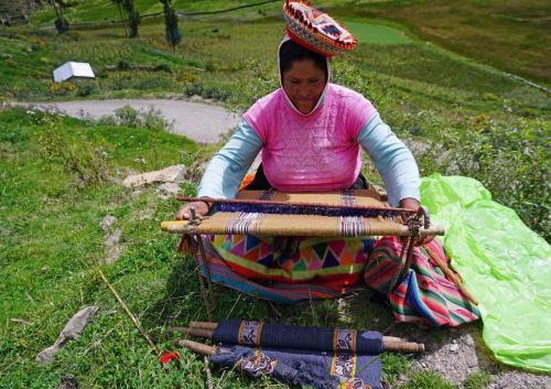 Woman weaving on mountainside