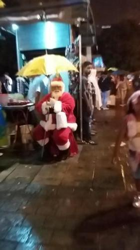 Santa under an umbrella because it is raiing