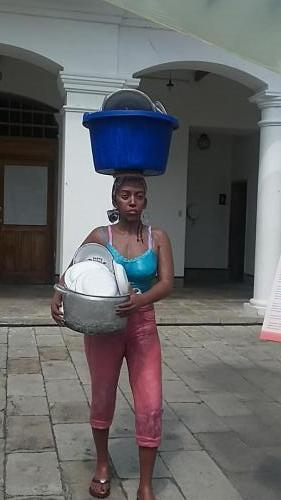 Lady carrying basket on head and things in her arms
