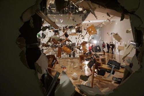 """Art exhibit showing hole in wall from an """"explosion"""""""